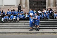 Μικρά παιδιά από τη σχολική συνεδρίαση στα βήματα της εισόδου στον της Λίμα καθεδρικό ναό στο Περού Στοκ φωτογραφία με δικαίωμα ελεύθερης χρήσης