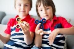 Μικρά παιδιά, αδελφοί αγοριών, που παίζουν με τη ζωηρόχρωμη fidget περιστροφή Στοκ φωτογραφία με δικαίωμα ελεύθερης χρήσης