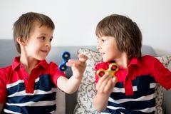 Μικρά παιδιά, αδελφοί αγοριών, που παίζουν με τη ζωηρόχρωμη fidget περιστροφή Στοκ Εικόνες