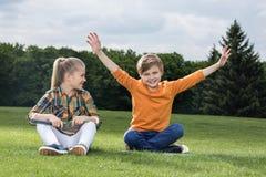 Μικρά παιδιά με τις ρακέτες μπάντμιντον που έχουν τη διασκέδαση καθμένος στη χλόη Στοκ εικόνα με δικαίωμα ελεύθερης χρήσης