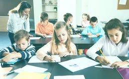 Μικρά παιδιά με το δάσκαλο στην τάξη Στοκ εικόνα με δικαίωμα ελεύθερης χρήσης