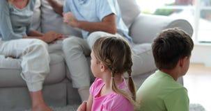 Μικρά παιδιά που ακούνε τους γονείς τους που παλεύουν στον καναπέ απόθεμα βίντεο