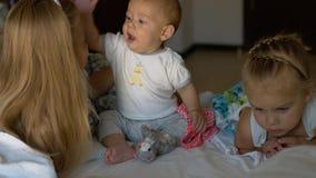 Μικρά παιδιά που κάθονται στο κρεβάτι και που παίζουν το ένα με το άλλο Στοκ φωτογραφία με δικαίωμα ελεύθερης χρήσης