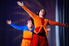 Μικρά παιδιά που χορεύουν με τα παλαιά ασιατικά κοστούμια στη σκηνή Στοκ Φωτογραφίες