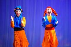 Μικρά παιδιά που χορεύουν με τα παλαιά ασιατικά κοστούμια στη σκηνή Στοκ φωτογραφία με δικαίωμα ελεύθερης χρήσης