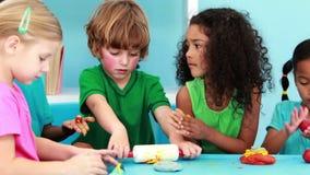 Μικρά παιδιά που χρησιμοποιούν τον άργιλο διαμόρφωσης φιλμ μικρού μήκους