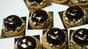 Μικρά στρογγυλά επιδόρπια σοκολάτας στον άσπρο δίσκο απόθεμα βίντεο