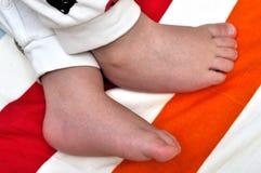 Μικρά τακούνια λίγου μωρού στο ριγωτό στρώμα στοκ φωτογραφία