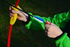 Μικρά χέρια αγοριών που φορτώνουν το βέλος στα παιδιά 15 φυλλόμορφων λίβρες τόξων έντασης Στοκ Εικόνες
