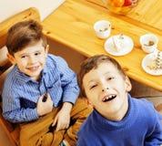 Μικρά χαριτωμένα αγόρια που τρώνε το επιδόρπιο στην ξύλινη κουζίνα designed home interior living retro room style Στοκ Εικόνες