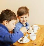 Μικρά χαριτωμένα αγόρια που τρώνε το επιδόρπιο στην ξύλινη κουζίνα designed home interior living retro room style Στοκ φωτογραφία με δικαίωμα ελεύθερης χρήσης