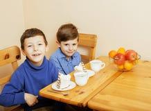 Μικρά χαριτωμένα αγόρια που τρώνε το επιδόρπιο στην ξύλινη κουζίνα designed home interior living retro room style χαμόγελο λατρευ Στοκ εικόνες με δικαίωμα ελεύθερης χρήσης