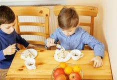Μικρά χαριτωμένα αγόρια που τρώνε το επιδόρπιο στην ξύλινη κουζίνα designed home interior living retro room style χαμόγελο λατρευ Στοκ Εικόνες