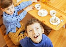 Μικρά χαριτωμένα αγόρια που τρώνε το επιδόρπιο στην ξύλινη κουζίνα designed home interior living retro room style χαμόγελο λατρευ Στοκ φωτογραφία με δικαίωμα ελεύθερης χρήσης