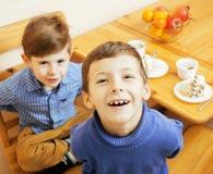 Μικρά χαριτωμένα αγόρια που τρώνε το επιδόρπιο στην ξύλινη κουζίνα designed home interior living retro room style χαμογελώντας λα Στοκ φωτογραφία με δικαίωμα ελεύθερης χρήσης