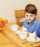 Μικρά χαριτωμένα αγόρια που τρώνε το επιδόρπιο στην ξύλινη κουζίνα designed home interior living retro room style χαμογελώντας λα Στοκ εικόνα με δικαίωμα ελεύθερης χρήσης