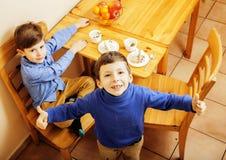 Μικρά χαριτωμένα αγόρια που τρώνε το επιδόρπιο στην ξύλινη κουζίνα designed home interior living retro room style χαμογελώντας λα Στοκ Εικόνες