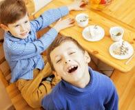 Μικρά χαριτωμένα αγόρια που τρώνε το επιδόρπιο στην ξύλινη κουζίνα designed home interior living retro room style χαμόγελο λατρευ Στοκ Φωτογραφία