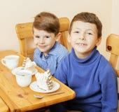 Μικρά χαριτωμένα αγόρια που τρώνε το επιδόρπιο στην ξύλινη κουζίνα designed home interior living retro room style χαμογελώντας λα Στοκ Φωτογραφία