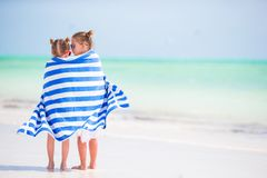 Μικρά χαριτωμένα κορίτσια που τυλίγονται στην πετσέτα στην τροπική παραλία Παιδιά στις διακοπές παραλιών Στοκ εικόνες με δικαίωμα ελεύθερης χρήσης