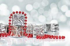 Μικρά δώρα Χριστουγέννων στο λαμπρό ασημένιο έγγραφο και τις κόκκινες tinsel χάντρες Στοκ Εικόνα
