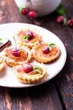 Μικρά tarts καραμέλας της Apple στο άσπρο πιάτο και το καφετί αγροτικό υπόβαθρο Γαλλικό tatin με το μήλο παραδείσου Στοκ Φωτογραφία