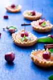 Μικρά tarts καραμέλας της Apple στο μπλε αγροτικό υπόβαθρο Γαλλικό tatin με το μήλο παραδείσου Στοκ Φωτογραφίες