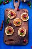 Μικρά tarts καραμέλας της Apple στον ξύλινο πίνακα και το μπλε αγροτικό υπόβαθρο Γαλλικό tatin με το μήλο παραδείσου Τοπ όψη Στοκ Εικόνες