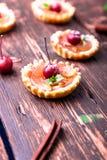 Μικρά tarts καραμέλας της Apple στο καφετί αγροτικό υπόβαθρο Γαλλικό tatin με το μήλο παραδείσου Στοκ Εικόνες