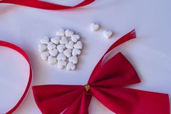 μικρές άσπρες καρδιές σε ένα άσπρο υπόβαθρο με την κόκκινα κορδέλλα και το τόξο στοκ εικόνα