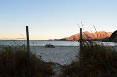 Μικρές ίχνος και πύλη μπροστά από την άσπρη άμμο παραλιών με τον ωκεανό και το βουνό Στοκ Εικόνα
