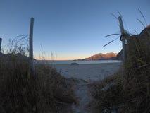 Μικρές ίχνος και πύλη μπροστά από την άσπρη άμμο παραλιών με τον ωκεανό και το βουνό Στοκ Εικόνες
