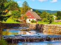 Μικρές αγροτικές εξοχικό σπίτι βουνών και παιδική χαρά κήπων στο μικρό ρεύμα Αγροτικό τοπίο την ηλιόλουστη ημέρα Στοκ Φωτογραφία