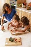 Μικρές αδελφές που μαγειρεύουν με τη μητέρα της στην κουζίνα Στοκ Εικόνες