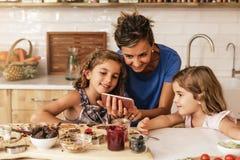 Μικρές αδελφές που μαγειρεύουν με τη μητέρα της στην κουζίνα Στοκ εικόνες με δικαίωμα ελεύθερης χρήσης