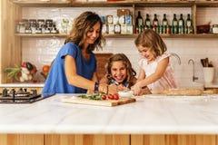 Μικρές αδελφές που μαγειρεύουν με τη μητέρα της στην κουζίνα Στοκ φωτογραφία με δικαίωμα ελεύθερης χρήσης