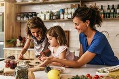 Μικρές αδελφές που μαγειρεύουν με τη μητέρα της στην κουζίνα Στοκ εικόνα με δικαίωμα ελεύθερης χρήσης