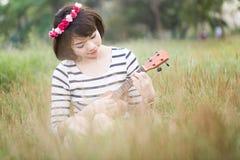 Μικρές ασιατικές γυναίκες που κάθονται στη χλόη και το παιχνίδι ukulele Στοκ Φωτογραφία