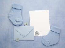 Μικρές κάλτσες αγοριών, κενή κάρτα και evelop στο μπλε υπόβαθρο υφάσματος Επίπεδος βάλτε Στοκ Φωτογραφία