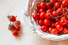 Μικρές κόκκινες ντομάτες κερασιών σε ένα ψάθινο καλάθι σε έναν παλαιό ξύλινο πίνακα Στοκ Εικόνες