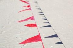 Μικρές κόκκινες σημαίες ενάντια μπλε σε πονηρό Στοκ εικόνες με δικαίωμα ελεύθερης χρήσης