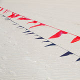 Μικρές κόκκινες σημαίες ενάντια μπλε σε πονηρό Στοκ Εικόνα