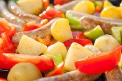 Μικρές λουκάνικα, πατάτες και ντομάτες σε ένα καυτό τηγάνι που μαγειρεύει έξω στον ήλιο στοκ εικόνες