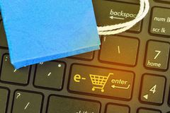 Μικρές μπλε τσάντες αγορών εγγράφου στο πληκτρολόγιο σημειωματάριων Περιμένετε  στοκ φωτογραφία με δικαίωμα ελεύθερης χρήσης