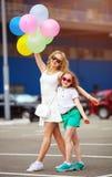 Μικρές παιδί και αδελφή στα γυαλιά ηλίου που έχουν τη διασκέδαση υπαίθρια με τα μέρη των ζωηρόχρωμων μπαλονιών Στοκ Φωτογραφία