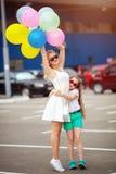 Μικρές παιδί και αδελφή στα γυαλιά ηλίου που έχουν τη διασκέδαση υπαίθρια με τα μέρη των ζωηρόχρωμων μπαλονιών Στοκ εικόνες με δικαίωμα ελεύθερης χρήσης