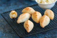 Μικρές πολτοποιηίδες πίτες χεριών πιτών πατατών σε ένα ράφι καλωδίων Μπλε sto Στοκ Εικόνες