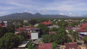 Μικρές προαστιακές στέγες πόλης κοινοτικές κατοικίας, θέα βουνού Κεραία κηφήνων απόθεμα βίντεο