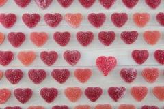 Μικρές σκούρο κόκκινο και ρόδινες Gummy καρδιές με ένας μεγαλύτερος διαβασμένου Gummy Στοκ Εικόνες