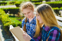 Μικρές όμορφες μαθήτριες που διαβάζουν ένα βιβλίο και που κάθονται στον πάγκο υπαίθριο Στοκ εικόνα με δικαίωμα ελεύθερης χρήσης